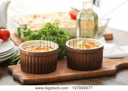 Ramekins with delicious turkey casserole on table