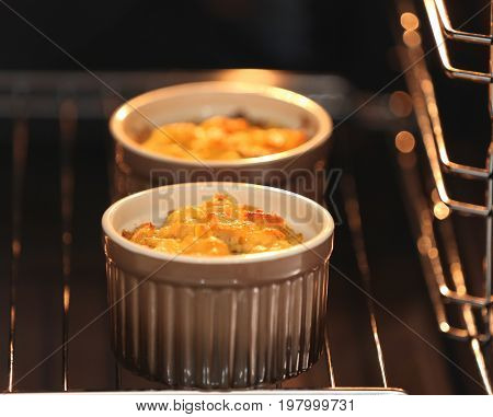 Ramekins with delicious turkey casserole in oven