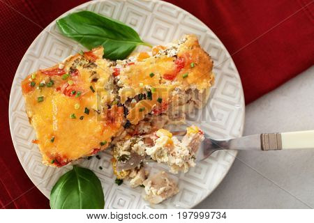 Plate and fork with delicious turkey casserole on table