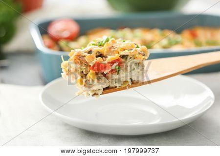 Spatula with piece of delicious turkey casserole, closeup