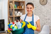 Studio shot of housekeeper. Beautiful woman cleaning office. Woman wearing gloves, smiling, showing thumb up and holding bowl full of bottles with disinfectant poster