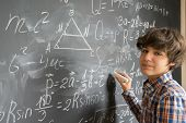 Handsome teenage Boy with chalk writting complicated math formulas on black board poster