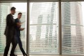 Busy businesspeople in office building, two businessmen walking along hallway, full-length window city view at background, running in hurry, business rush in lobby, working atmosphere, motion blur poster