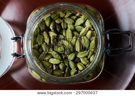 Closeup Proto Of Glass Jar Full Of Green Cardamom Pods On Brown Plate. Top View.