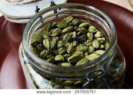 Closeup Proto Of Glass Jar Full Of Green Cardamom Pods On Brown Plate.