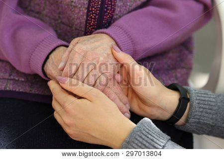 Hands Of Young Adult And Senior Women. Senior And Young Holding Hands Outside. Elderly Concept