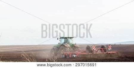 Kiev, Ukraine - March 27, 2019: Agriculture, Tractor Preparing Land With Seedbed Cultivator As Part