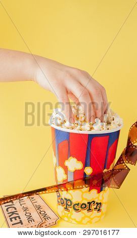 Hand Takes A Movie Tickets And Popcorn From A Paper Cup On A Yellow Background. Woman Eats Popcorn.