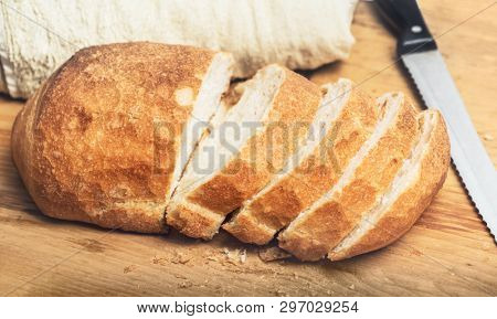 Ciabatta bread loaf slices on wooden board with knife. Fresh crusty white whreat bread italian cuisine
