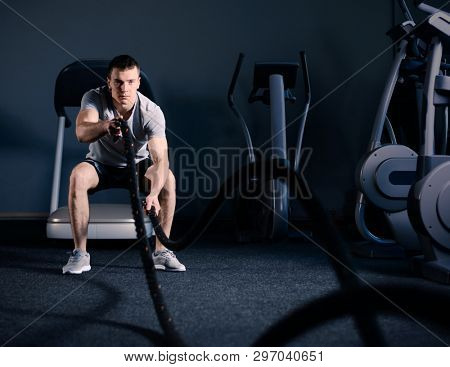 Muscular Man is Doing Battle Rope Exercise while Working out in Dark Modern Training Fitness Gym. CrossFit and Healthy Lifestyle Concept.