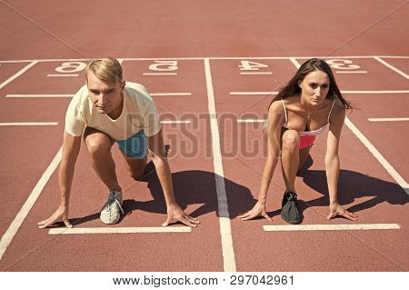 Equal Forces Concept. Man And Woman Low Start Position Running Surface Stadium. Running Competition
