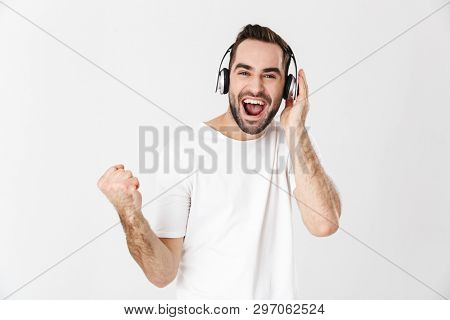 Handsome cheerful man wearing blank t-shirt standing isolated over white background, listening to music with headphones