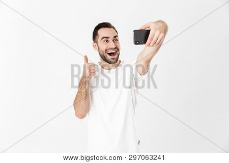 Handsome cheerful man wearing blank t-shirt standing isolated over white background