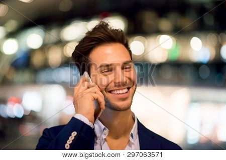 Young handsome man talking on the cell hone at night