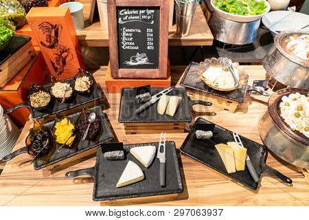 Variety of cheese on rustic wooden table in buffet line