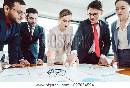 Team of business people analyzing numbers and charts spread out on the desk