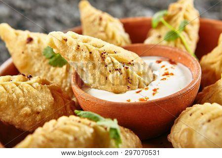 Azerbaijani Fried Dumplings Giurza with Minced lamb Meat also known as Gyoza, Dim Sum, Jiaozi, Momo, Mandu or Ravioli Close Up. Hot Crunchy Beef and Mutton Pelmeni on Natural Rustic Bakground