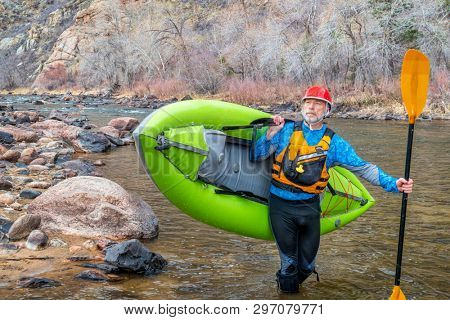 senior paddler carrying inflatable whitewater kayak on a shore of mountain river in early spring - Poudre River above Fort Collns, Colorado