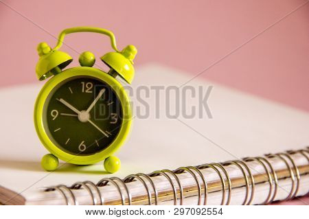 A Small Green Alarm Clock Is Standing On A White Notepad On A Pink Background. The Clock Shows The T