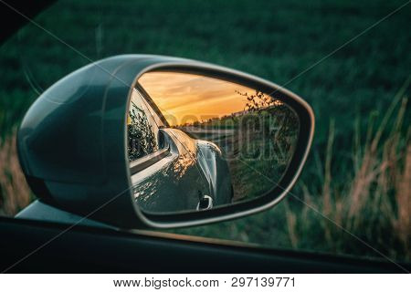 Beautiful Sunset In The Sideview Mirror Of A Car. Green Nature Background