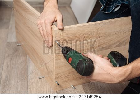 Assembling Furniture. Men's Hands With A Screwdriver To Collect New Furniture