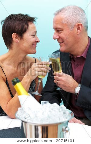 Photo of a mature married couple celebrating with a glass of champagne in a restaurant.