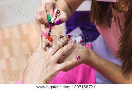 Close Up Of Female Hands Applying Magenta Color