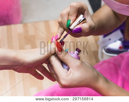Close Up Of Female Hands Applying Magenta Nail Color