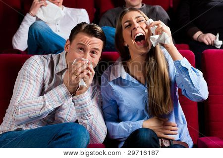 Couple and other people, probably friends, in cinema watching a movie; it seems to be a funny movie