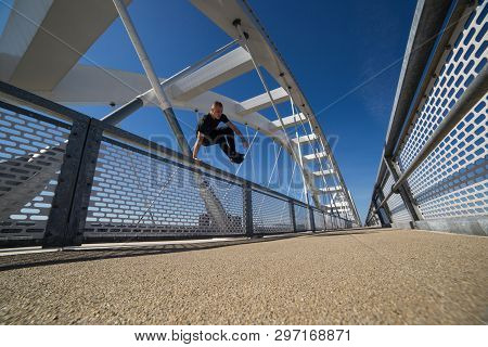 Attractive Young Man Jumping On The New Bridge.