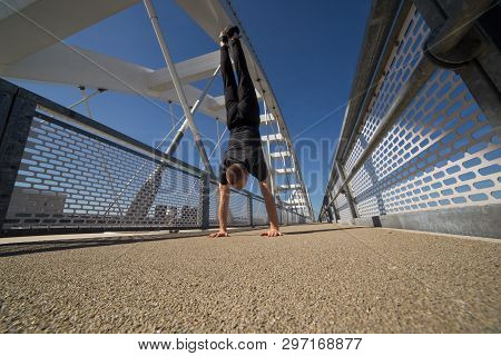Strong Young Athlete Doing Handstand On The Bridge
