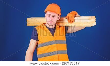 Man In Helmet, Hard Hat And Protective Gloves Holds Wooden Beam, Blue Background. Carpenter, Woodwor