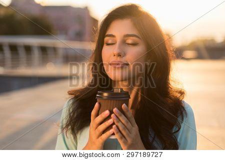 Tranquil Girl Enjoying Takeaway Coffee, Walking In City At Sunset