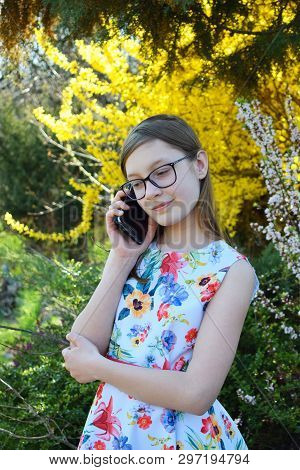 Portrait Of Beautiful Girl With Glasses And Brown Hair Talk On Smart Phone. Young Smiling Teneeger I
