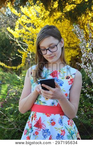 Portrait Of Beautiful Girl With Glasses And Brown Hair Typing Write Message On Smart Phone. Young Sm