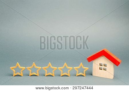 Five Stars And A Wooden House On A Gray Background. The Concept Of The Best Housing, Luxury Apartmen