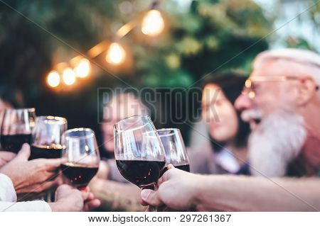 Happy Family Eating And Drinking Red Wine At Dinner Barbecue Party Outdoor - Mature And Young People