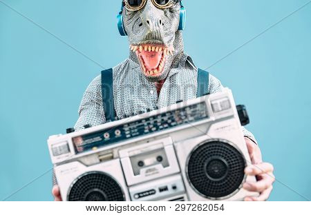 Crazy Senior Man Wearing T-rex Mask And Listening To Music Holding Vintage Boombox Stereo Outdoor -