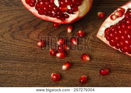 still life - red whole and cut pomegranate fruits and scattered seeds on a dark wooden tabletop poster