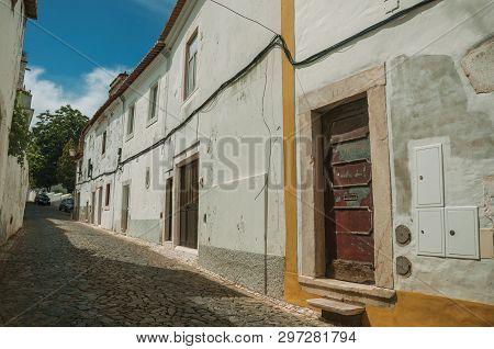 Old Houses With Doors On Alley With Cobblestone Pavement In Sunny Day At Estremoz. A Nice Little His
