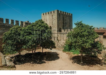 Stone Walls And Tower With Merlons Around Central Courtyard With Green Trees In A Sunny Day At The C