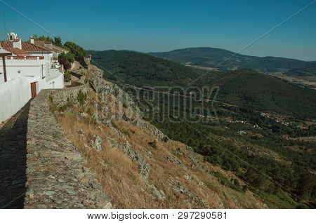Old Houses And Stone Breastwork Over Ridge, With Mountainous Landscape Covered By Trees In A Sunny D