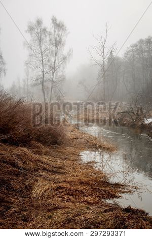 Misty Landscape With Forest And River At Early Morning