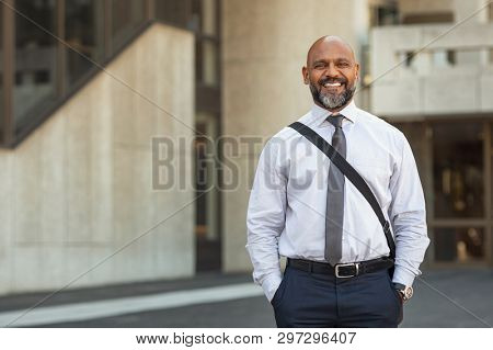 Happy mature businessman with laptop bag standing on street. Smiling business man in formal clothing looking at camera in the city centre. Black man going to work with building in the background.