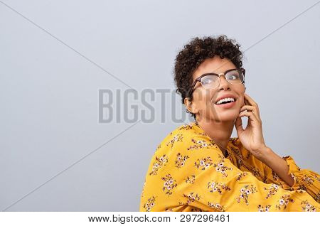 Happy thinking young woman looking away with fashion eyeglasses. African american female student thinking about future while isolated against grey wall. Brazilian with spectacles looking away.