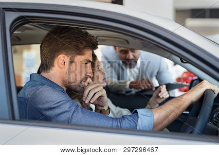 Serious dealer looking at pensive couple sitting in car to checking features. Young couple deciding to buy new auto in showroom with cardealer. Thoughtful man with his girlfriend at car dealership.