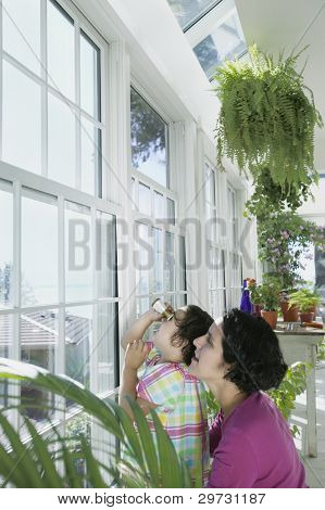 Mother and daughter looking out window of greenhouse