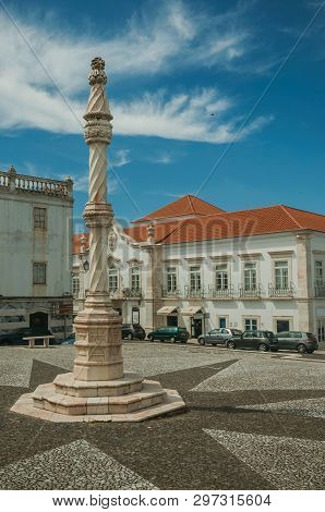 Estremoz, Portugal - July 6, 2018. Pillory in the foreground on square with old buildings around in sunny day at Estremoz. A nice little historic town with several marble buildings on eastern Portugal