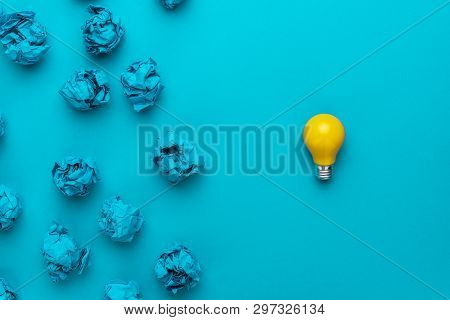 poster of new idea concept with crumpled office paper and light bulb. top view of great business idea concept over blue background. creative idea solution during brainstorming session concept