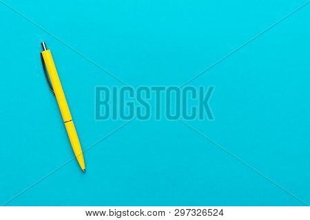 Top View Of Ballpoint Pen On The Blue Background. Minimalist Flat Lay Photo Of Yellow Pen Over Turqu